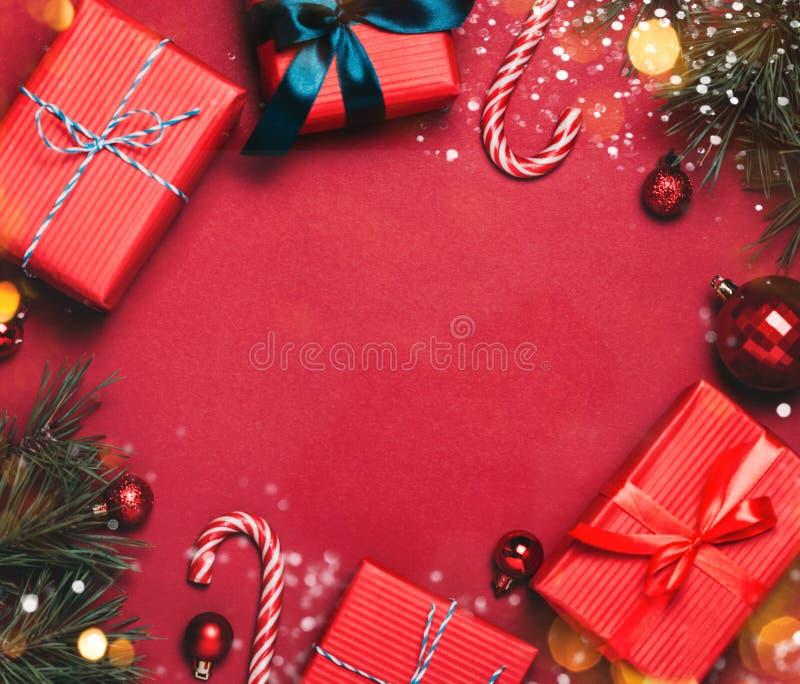 Fundo vermelho do Natal com bolas do Natal e para apresentar com os doces e a neve que caem neles fotografia de stock