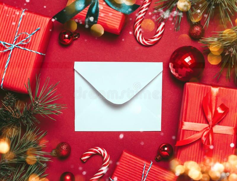 Fundo vermelho do Natal com bolas do Natal e para apresentar com os doces e a neve que caem neles foto de stock