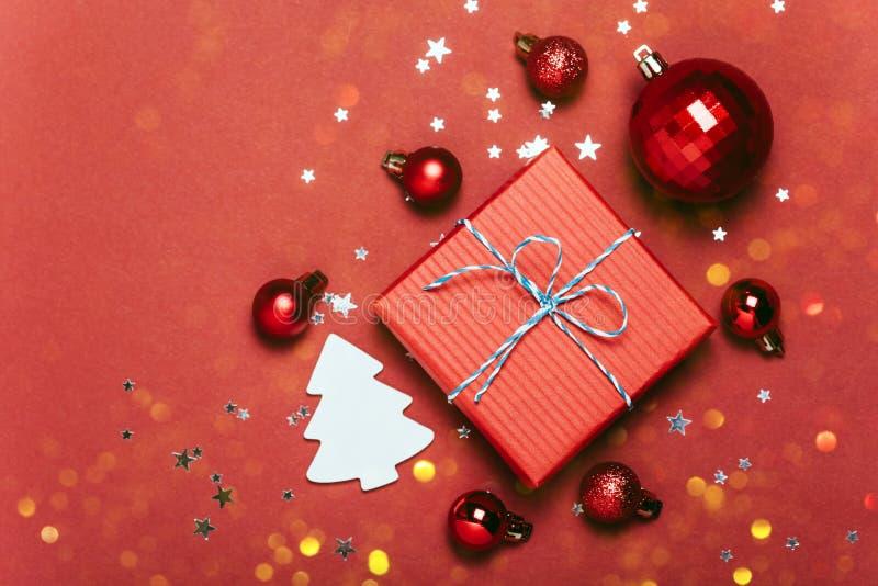 Fundo vermelho do Natal com bolas do Natal e para apresentar com os doces e a neve que caem neles imagens de stock