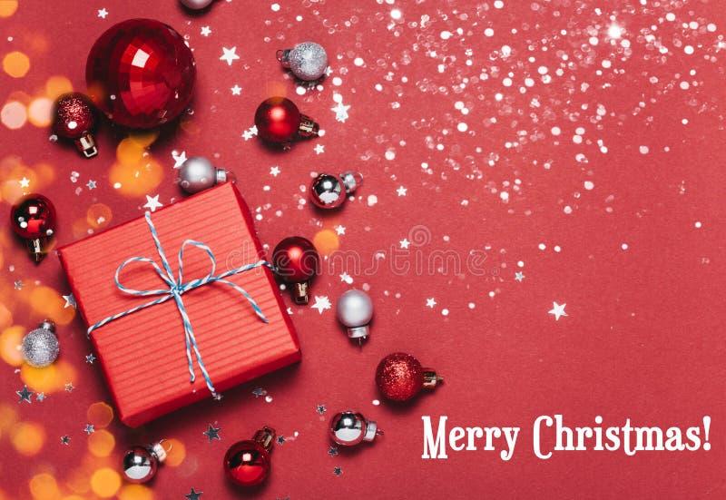 Fundo vermelho do Natal com bolas do Natal e para apresentar com os doces e a neve que caem neles fotos de stock
