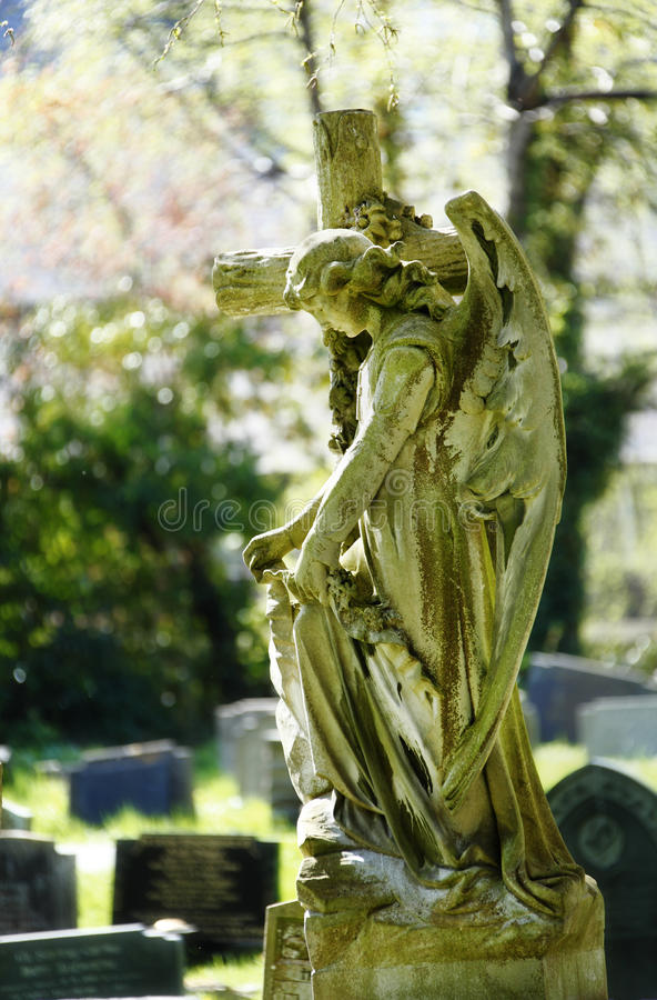 Funeral. Old graveyard with head stones and angel with cross after funeral. Memorial day concept royalty free stock photography