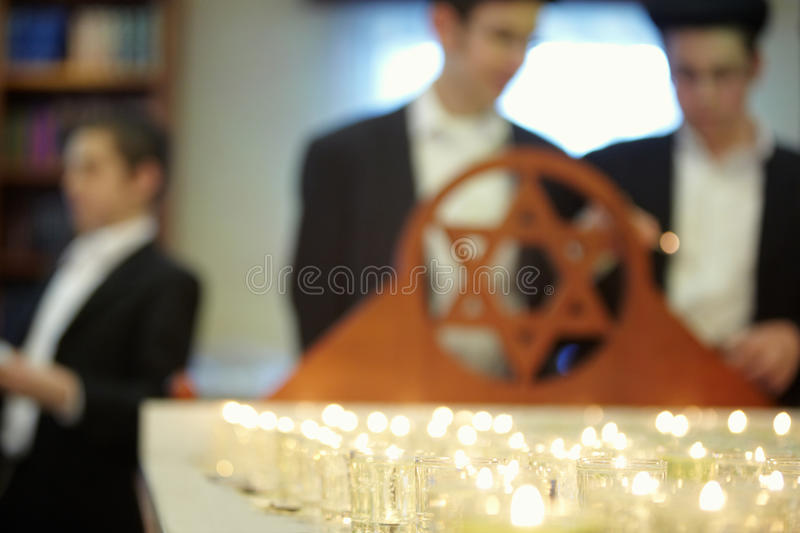 Funeral candles and star of David. Peoples on background not in focus stock photography