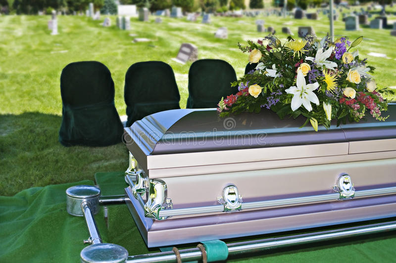 Funeral Casket. Image of a steel Casket with Flowers on top in a cemetery royalty free stock photos