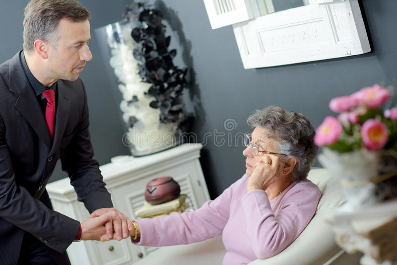 Funeral director holding hand elderly lady royalty free stock photo