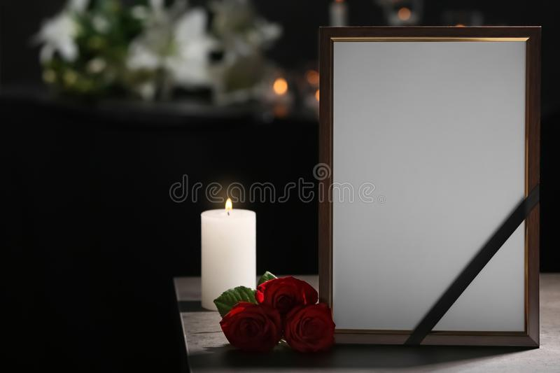 Funeral photo frame with black ribbon, roses royalty free stock photography