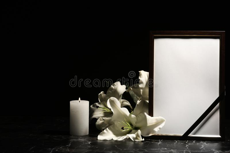Funeral photo frame, burning candle and lily flowers stock images