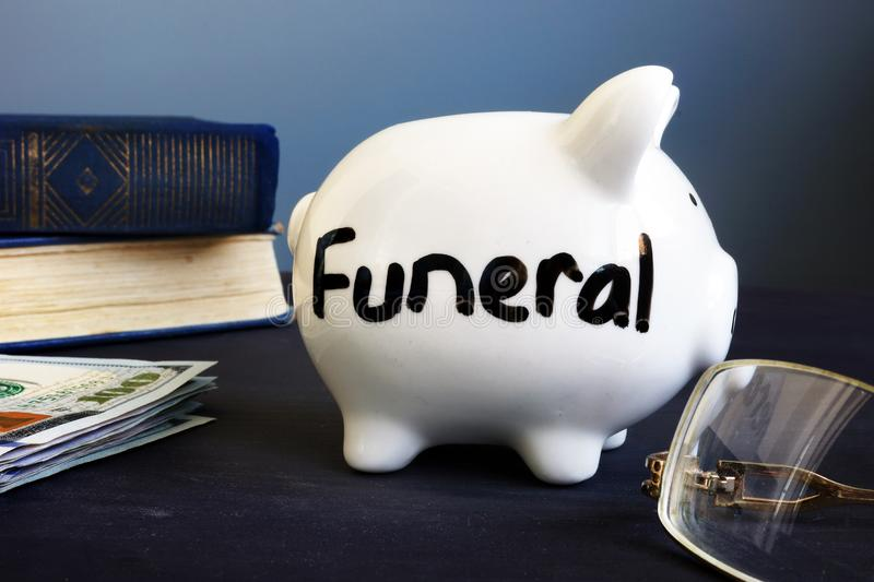 Funeral plan written on a side of piggy bank. Funeral plan written on the side of piggy bank stock image