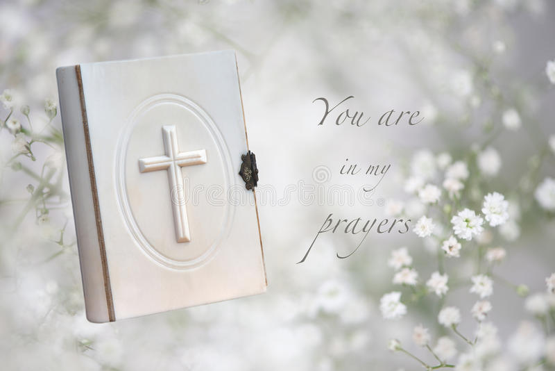 Funeral Prayers Card. Funeral card showing white prayer book and You are in my prayers message; babys-breath flowers in the background as a symbol for purity royalty free stock images