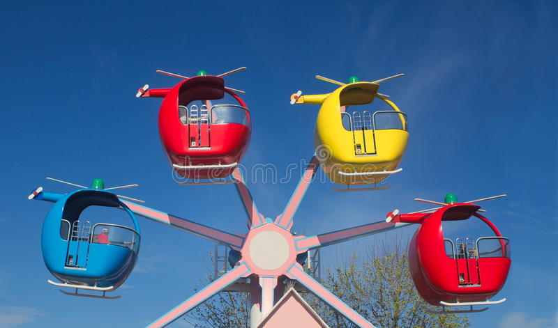 Funfair helicopter ride against a bright blue sky stock images