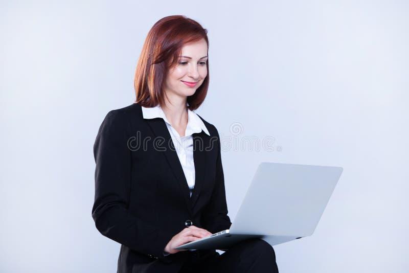 fungerande barn för affärsbärbar datorkvinna Attraktiv mogen affärskvinna som arbetar på bärbara datorn royaltyfria bilder