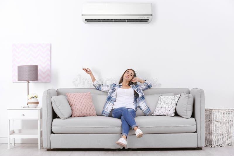 Fungerande luftkonditioneringsapparat för ung kvinna, medan sitta royaltyfri foto