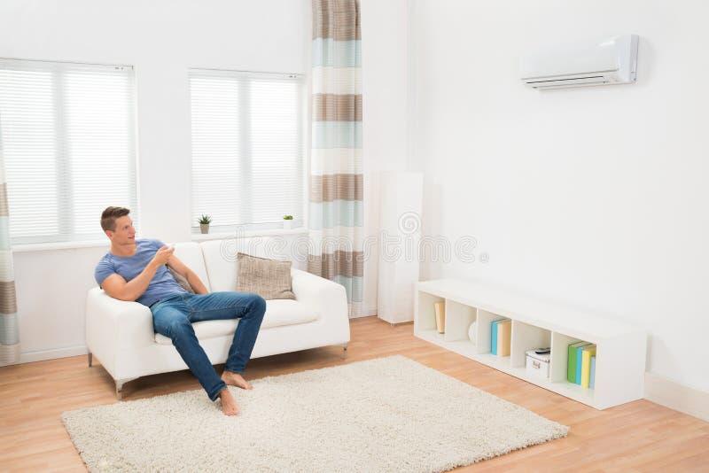 Fungerande luftkonditioneringsapparat för ung man fotografering för bildbyråer