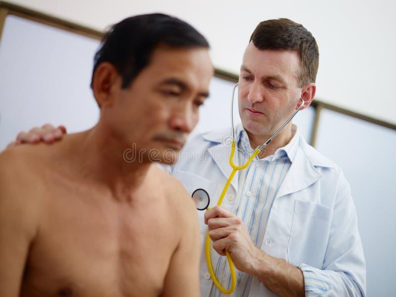 Fungerande och besök gamal man för doktor i klinik royaltyfria bilder