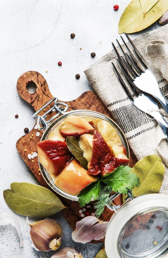 Funghi bianchi salati o marinati in barattolo di vetro con le spezie e le erbe, cucinanti concetto d'inscatolamento dell'alimento immagine stock