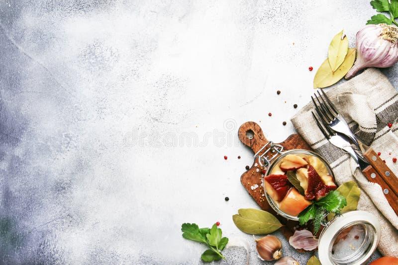 Funghi bianchi salati o marinati in barattolo di vetro con le spezie e le erbe, cucinanti concetto d'inscatolamento dell'alimento fotografia stock libera da diritti