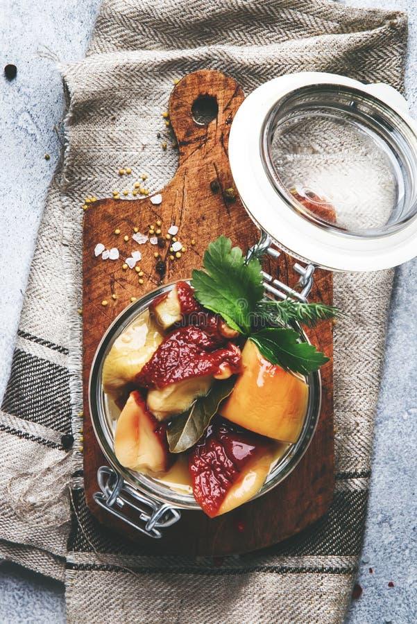 Funghi bianchi salati o marinati in barattolo di vetro con le spezie e le erbe, cucinanti concetto d'inscatolamento dell'alimento fotografia stock