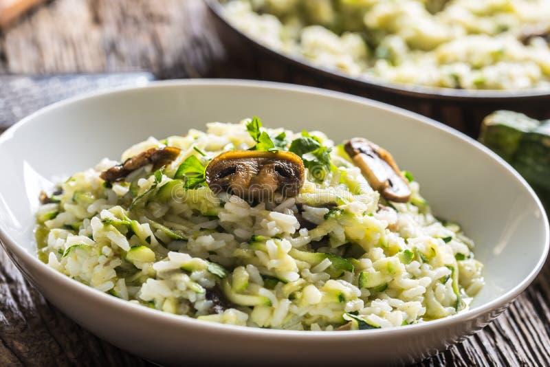 Funghi e parmigiano italiani dello zucchini del risotto in piatto bianco fotografia stock