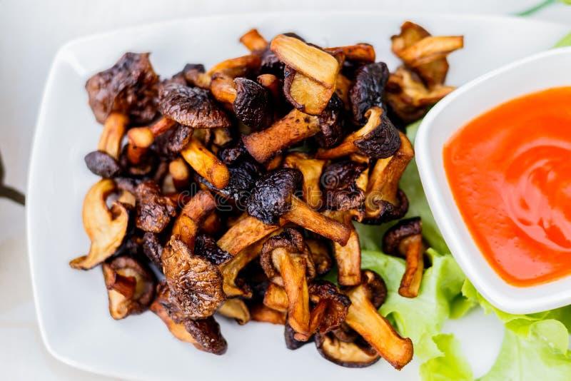 Funghi fritti con sale e pepe sul piatto bianco immagine stock libera da diritti