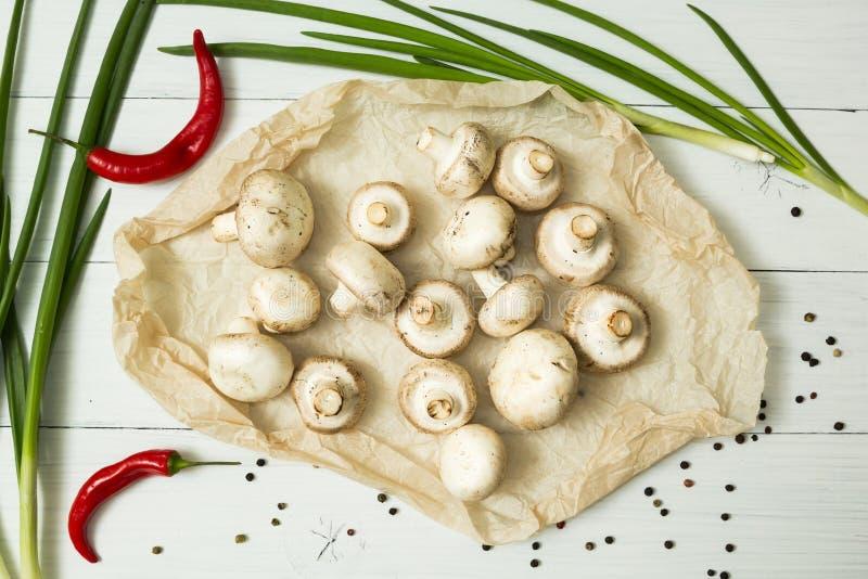 Funghi organici freschi su un fondo di legno bianco, accanto ad un peperoncino rosso, alle cipolle verdi ed alle spezie fotografia stock libera da diritti