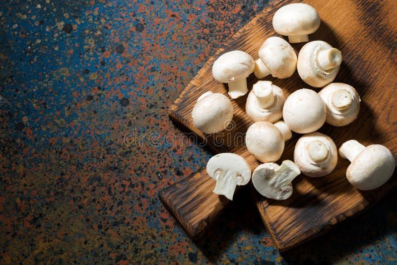 Funghi organici freschi sul tagliere d'annata, vista superiore fotografia stock libera da diritti