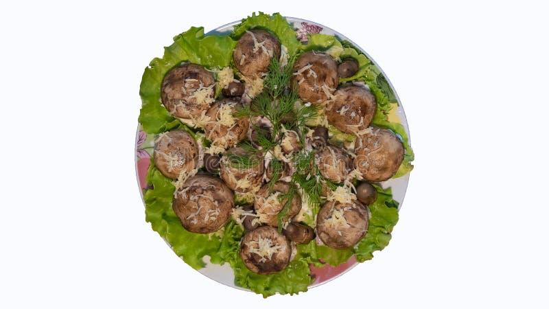 Funghi prataioli con formaggio fuso sulle foglie del cavolo, vista superiore, piatto saporito immagine stock