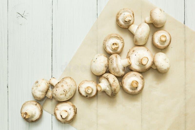 Funghi prataioli freschi dei funghi su un fondo di legno bianco immagini stock