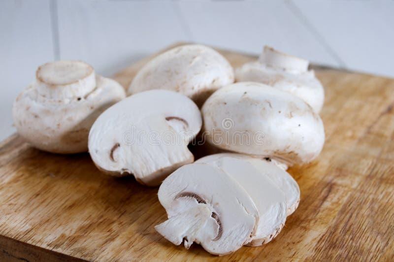 Funghi prataioli freschi su un tagliere di legno Su fondo di legno bianco immagine stock