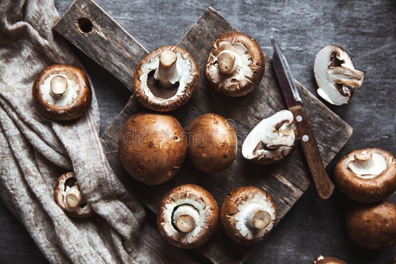 Funghi reali su un fondo nero con un bordo d'annata e un asciugamano di cucina fotografia stock