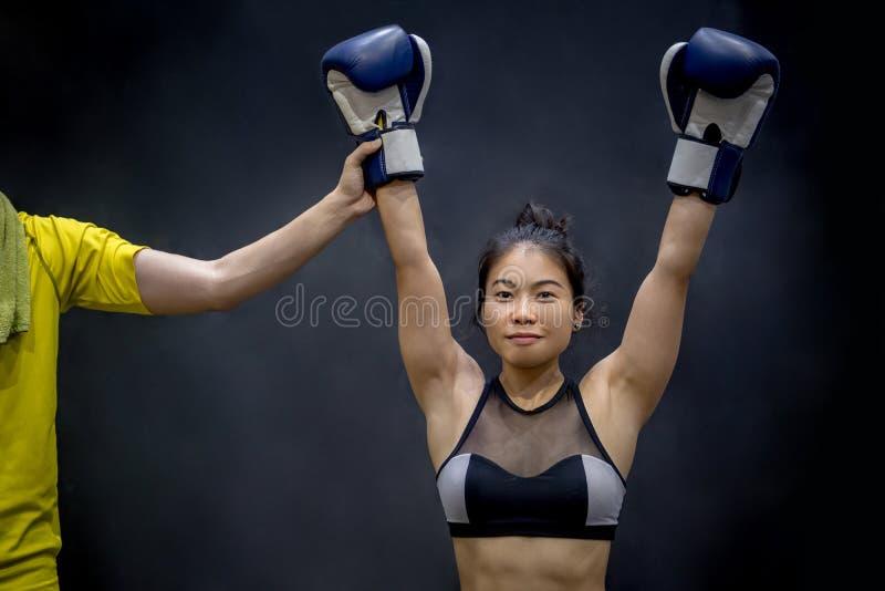 Fungieren Sie anhebende weibliche Boxerhand, Sieger des Matches als Schiedsrichter stockfoto