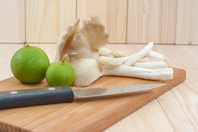Fungo di ostrica del Tibet sul tagliere di legno con il coltello e il lem immagine stock