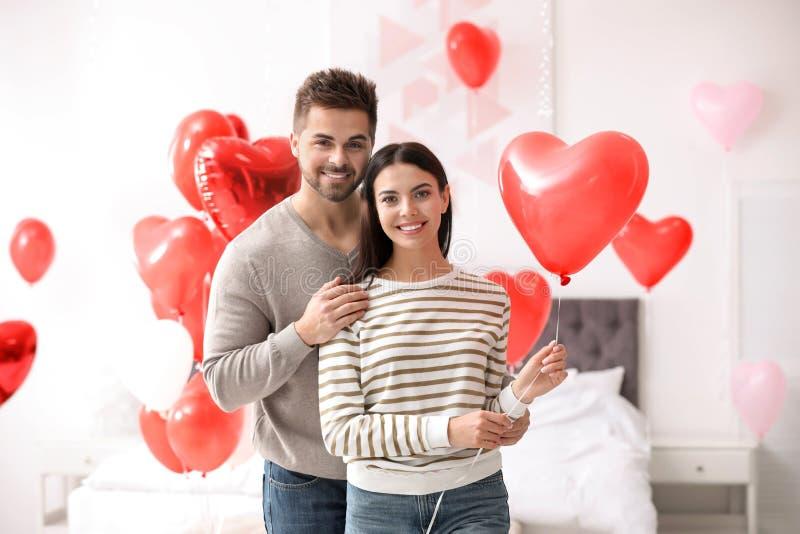 Fungt par med hjärtformade ballonger Alla hjärtans dag royaltyfri bild