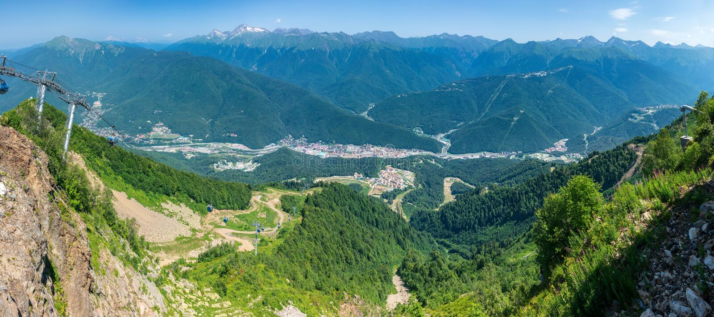 Funiculaire dans la montagne Vue au-dessus des maisons résidentielles de vallée verte, entourées par de hautes montagnes nature photos libres de droits
