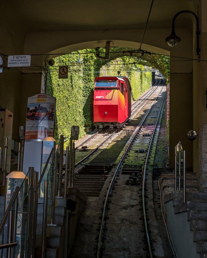 Funiculare San Vigilio - funicular rojo en la ciudad vieja de Bérgamo El funicular desciende a la estación más baja imagen de archivo