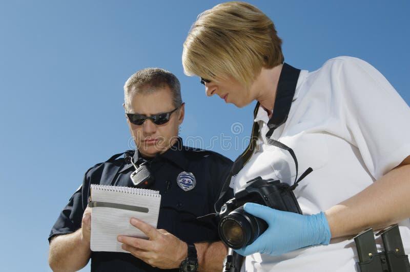 Funkcjonariusz Policji I oficer śledczy Z kamerą zdjęcia stock