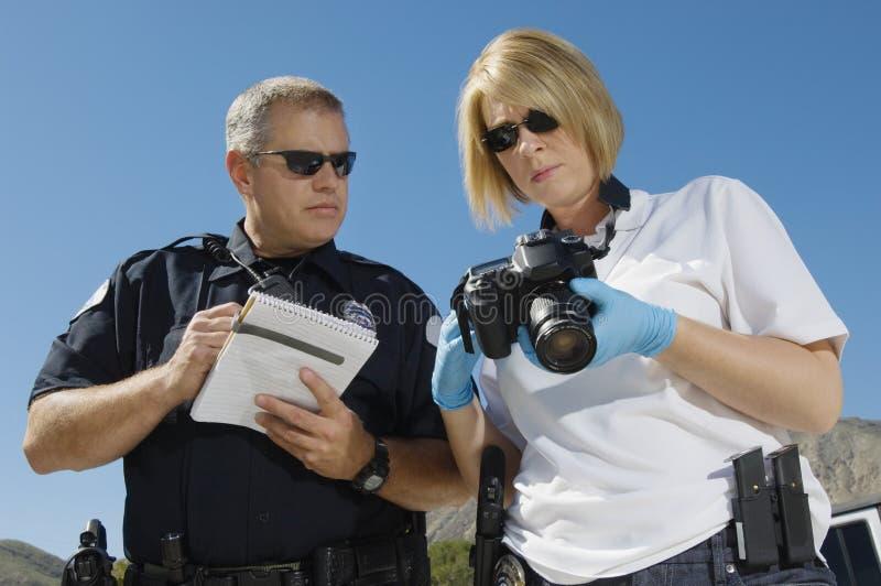 Funkcjonariusz Policji I oficer śledczy Z kamerą obraz royalty free