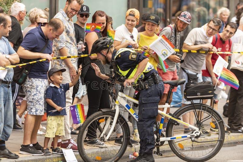 Funkcjonariusz policji robi wysokości z dzieciakiem Europride Sztokholm obrazy stock