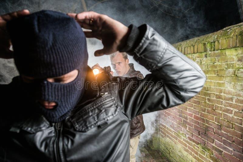 Funkcjonariusz policji wskazuje pistolet w kierunku psującego zamaskowanego włamywacza bri zdjęcia royalty free