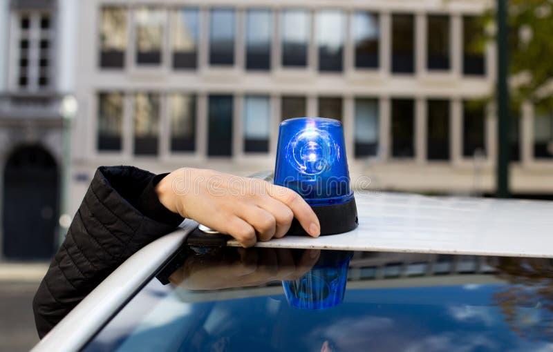 Funkcjonariusz policji wspina się płodozmiennego przeciwawaryjnego światło na samochodzie obrazy royalty free