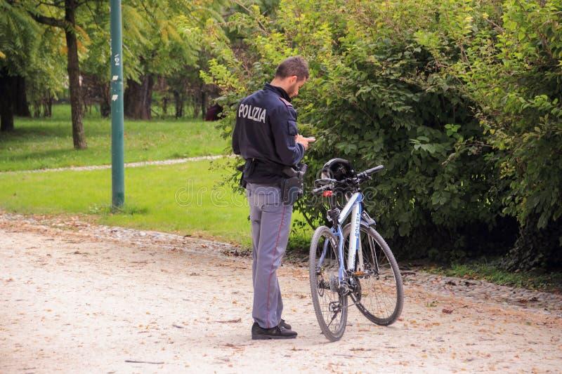 Funkcjonariusz policji z rowerową pozycją blisko w Sempione parkowym Sforzesco kasztel i patrzeć telefon komórkowego Mediolan, Wł fotografia royalty free