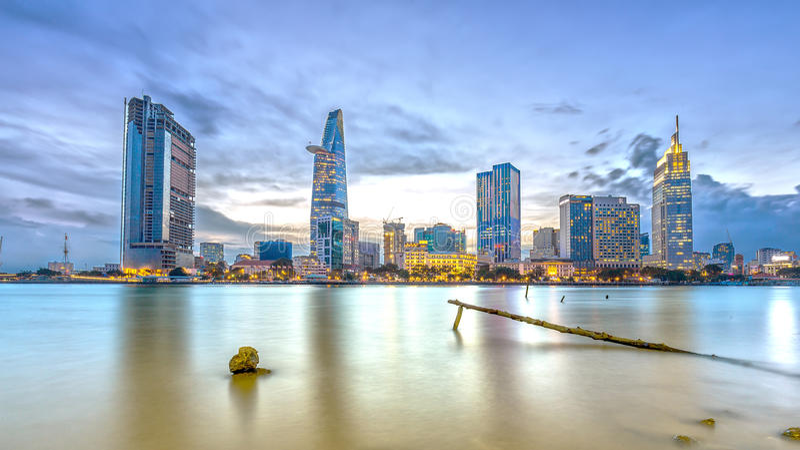 Funkelnde Wolkenkratzer der helleren Kohle des Flussufer-Stadtsonnenuntergangs entlang Fluss lizenzfreie stockbilder