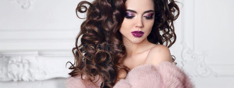 Funkelnschönheitsmake-up Brunette mit gelockter Frisur trägt in p lizenzfreies stockbild