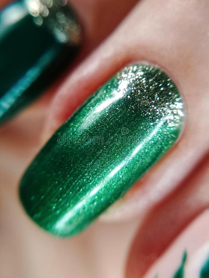 Funkelnschimmermaniküregel-Nagellack-Musterentwurfsschönheits-Mode des Frauenhandfingers Makrofoto der grünen silbernen stockbild