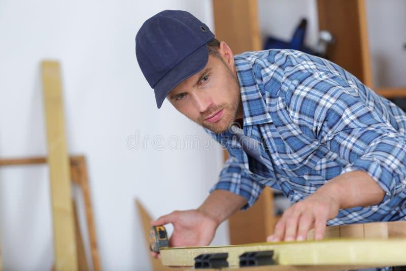 Funktion des jungen Mannes des Bildes als Tischler und messendes Brett lizenzfreie stockfotos