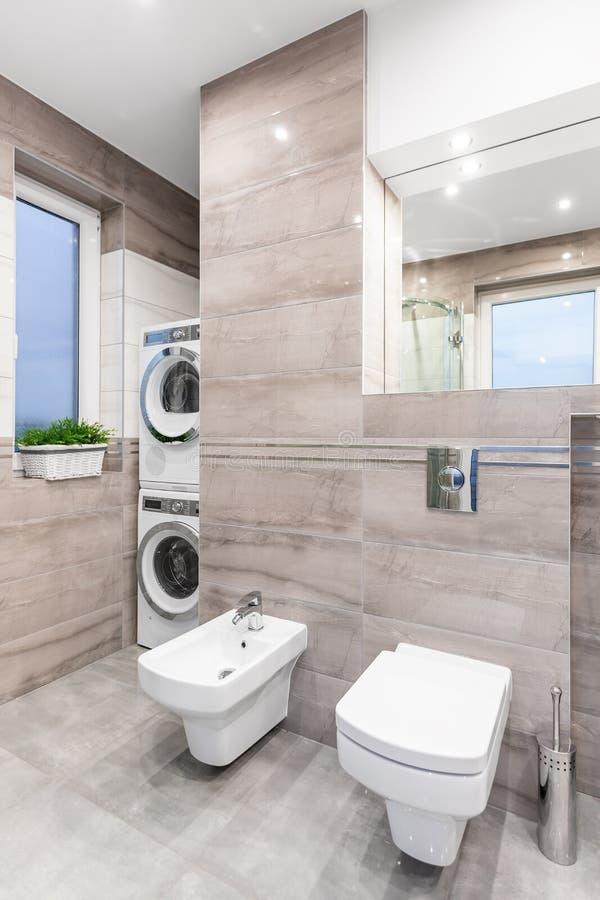 Funktionellt badrum i beige idé arkivbild