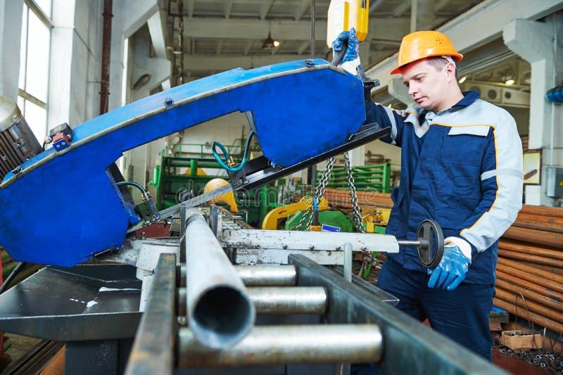 Funktionierende Bandsäge der industriellen männlichen Arbeitskraft in der Herstellungsfabrik lizenzfreie stockfotos