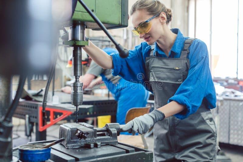Funktionierende Bohrmaschine der Metallarbeitskraftfrau lizenzfreie stockfotos