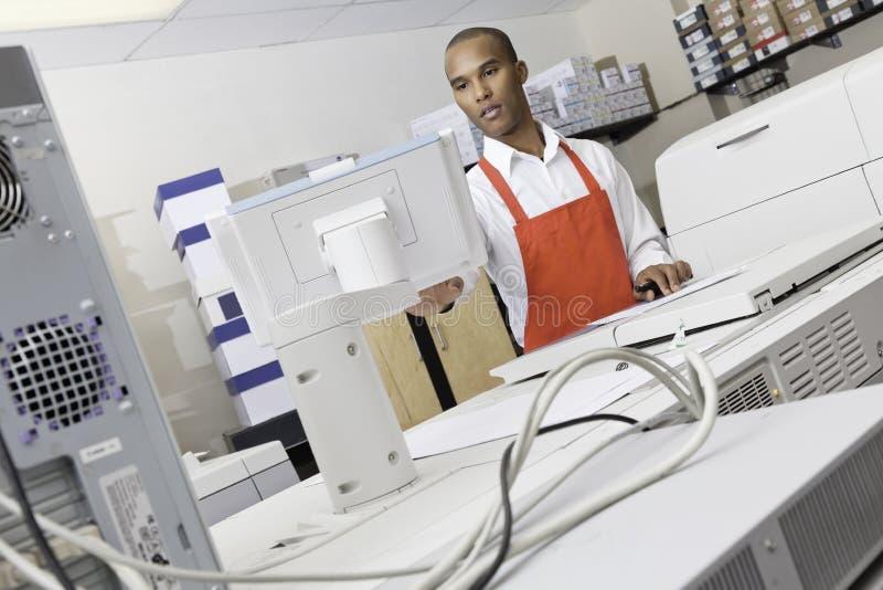 Funktionierende Maschine des Mannes Druckan der Presse stockfotos
