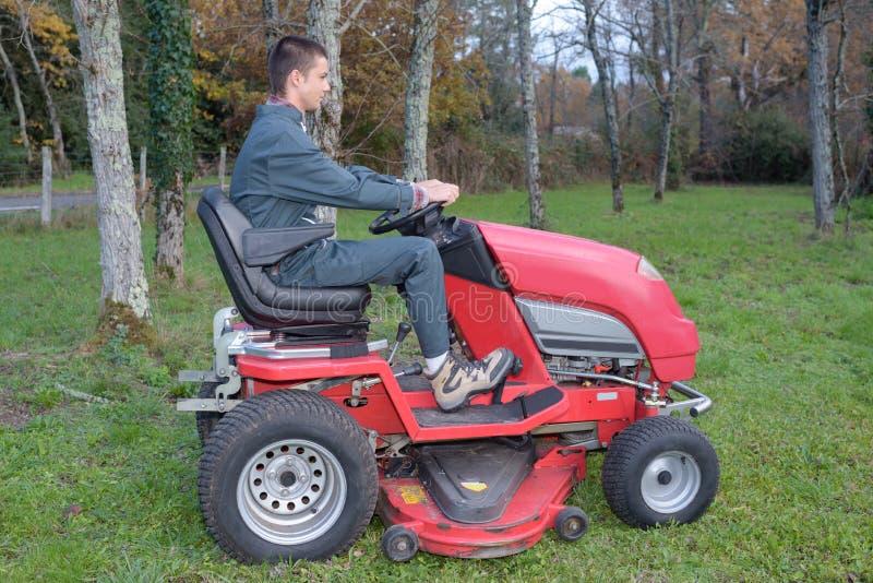 Funktionierender Gartentraktor des jungen Gärtners lizenzfreies stockbild