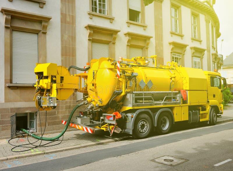 Funktionsduglig kloaklastbil som arbetar i stads- stadsmiljö fotografering för bildbyråer