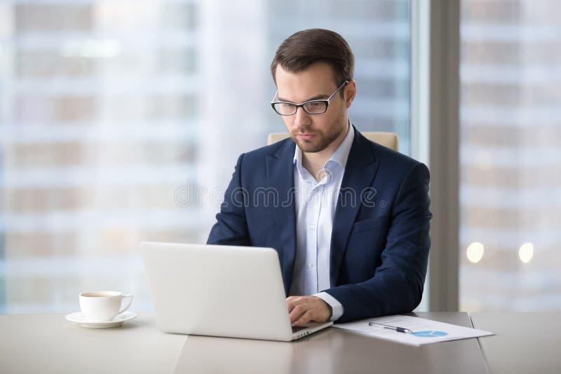 Funktionsduglig maskinskrivningbokstav för allvarlig affärsman på bärbara datorn royaltyfria bilder